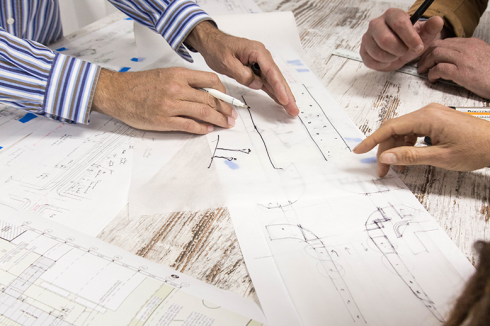 Hands pointing to design features on plans