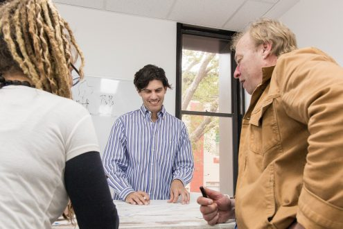 People smiling in an office environment demonstrating collaboration